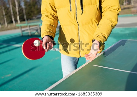guy plays table tennis pingpong on the street. racket and ball with a tennis green table. hands in the frame and racket. in a yellow jacket in cold weather Royalty-Free Stock Photo #1685335309