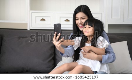 Mother and daughter are taking pictures in the living room.