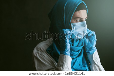 a doctor, a Muslim woman in a hijab and a protective medical bandage, was tired after taking a large number of patients as a result of the outbreak of the coronavirus #1685431141