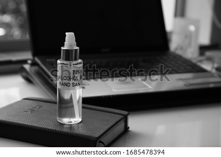Working from home during the Coronavirus (covid-19) pandemic concept image. This photo contains a bottle of used sanitizer, a diary and a business laptop.
