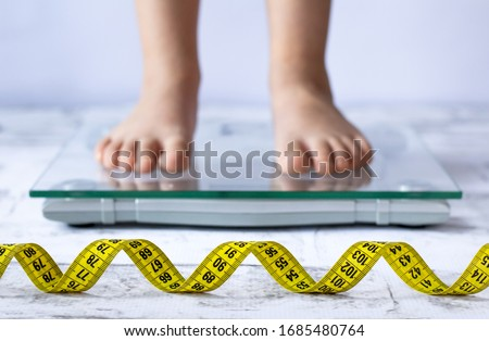 Weight control concept with centimeter in focus and blurred kid's feet on digital scale in the background. Child measuring weight, healthy growing.  #1685480764