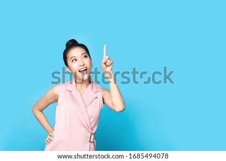 Portrait of Asian beautiful young woman pointing up one hand with finger on upper side with smile face. The pretty girl stand and looking at camera in studio. Advertisement & presentation concept.