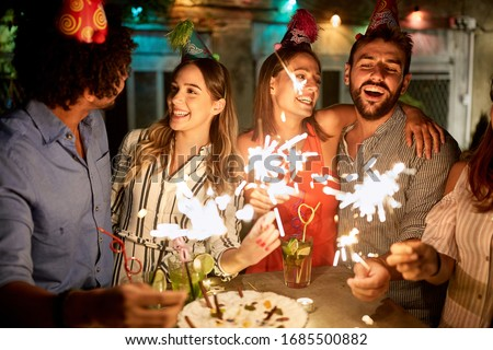 Happy female and male holding sparkles on birtday party Royalty-Free Stock Photo #1685500882