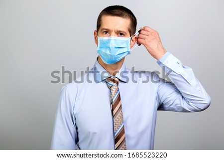 Business man in medical mask closed his mouth with his hand #1685523220