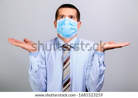 Business man in medical mask spreads his hands in the sides and looks up #1685523259