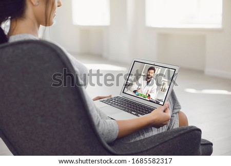 Online doctor.A sick young woman video chat with a male doctor at home. #1685582317