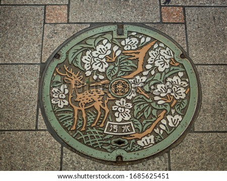 "A colourful manhole cover of Nara city with yellow deer and pink sakura flowers  pictures and Japanese word ""sewage"" on it. Nara, Japan."