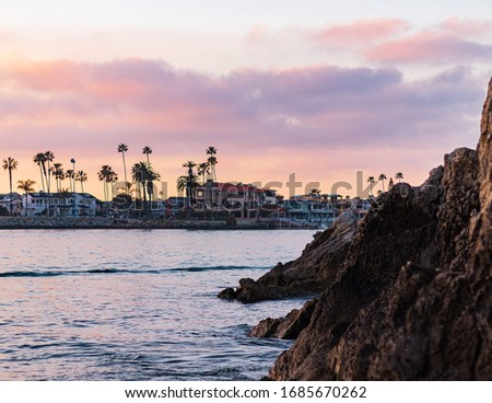 Sunset HDR photo of the of the ocean channel and bluffs located in the Southern California city of Corona Del Mar. Homes and palm trees are seen under a sunset sky.