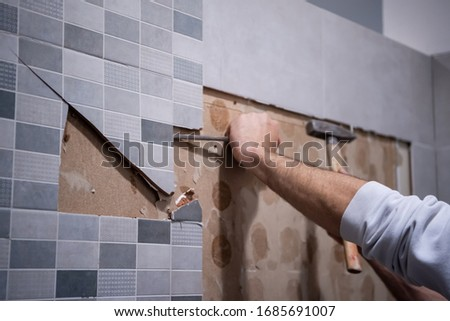 professional worker remove demolish old tiles in a bathroom with hammer and chisel #1685691007