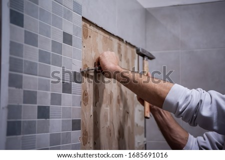 professional worker remove demolish old tiles in a bathroom with hammer and chisel Royalty-Free Stock Photo #1685691016