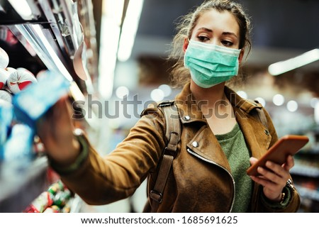 Young woman with face mask using mobile phone and buying groceries in the supermarket during virus pandemic.  #1685691625