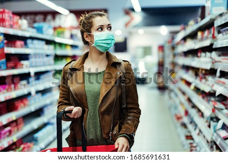 Young woman with face mask walking through grocery store during COVID-19 pandemic.  #1685691631