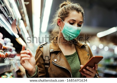 Young woman wearing protective mask on her face and reading shopping list on mobile phone in grocery store during virus pandemic.  #1685691634