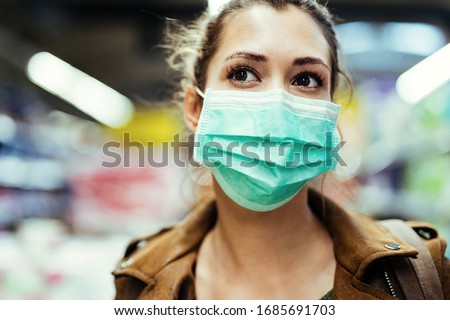 Close-up of woman wearing protective mask on her face while being in the store during coronavirus epidemic.  #1685691703