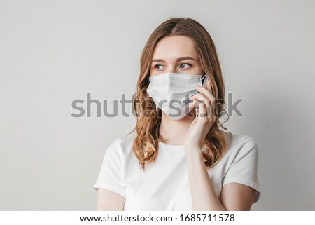 Young woman in a medical mask calls on the phone and stands over the wall and looks away isolated on a grey background, ordering goods, eating online, quarantine, isolation, coronovirus, copy space #1685711578
