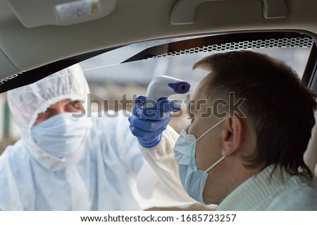 a doctor in a white protective medical suit with blue gloves measures the temperature with an electronic device in a masked car driver during an epidemic. COVID-19 CORONAVIRUS PANDEMIC #1685723257
