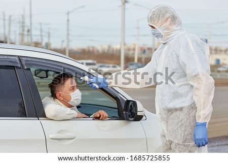 a doctor in a white protective medical suit with blue gloves measures the temperature with an electronic device in a masked car driver during an epidemic. COVID-19 CORONAVIRUS PANDEMIC #1685725855