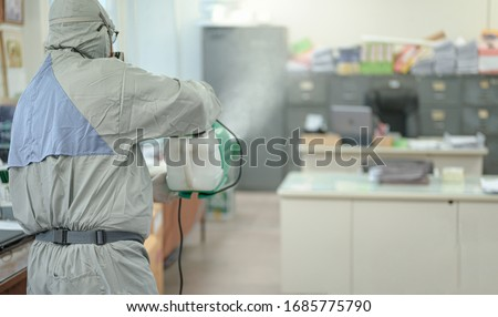 Disinfecting of office to prevent COVID-19, person in white hazmat suit with disinfect in office, Disinfectant worker wear protective mask and suit sprays coronavirus. #1685775790