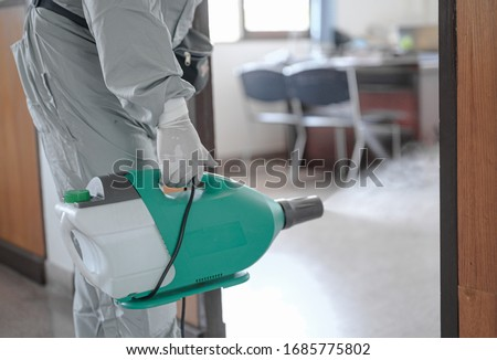 Disinfecting of office to prevent COVID-19, person in white hazmat suit with disinfect in office, coronavirus concept #1685775802