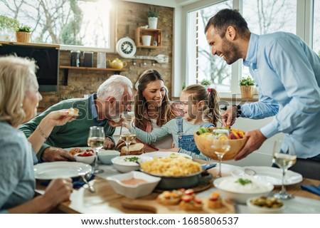 Happy multi-generation family gathering around dining table and having fun during a lunch.  #1685806537