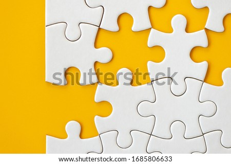 Puzzle pieces on orange background. White square puzzle pieces grid. Business background. Copy space for text, top view, close up. #1685806633