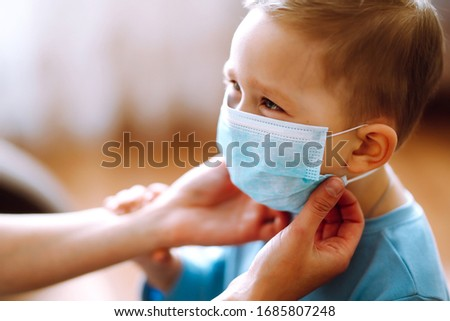 Little boy and mom in medical mask. Mother puts on her baby sterile medical mask. Child, wearing face mask, protect from infection of virus, pandemic, outbreak and epidemic of disease on quarantine. #1685807248
