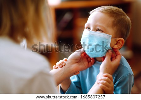 Little boy and mom in medical mask. Mother puts on her baby sterile medical mask. Child, wearing face mask, protect from infection of virus, pandemic, outbreak and epidemic of disease on quarantine. #1685807257