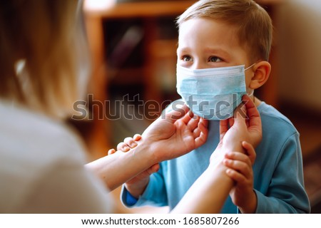 Little boy and mom in medical mask. Mother puts on her baby sterile medical mask. Child, wearing face mask, protect from infection of virus, pandemic, outbreak and epidemic of disease on quarantine. #1685807266