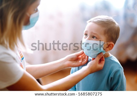 Little boy and mom in medical mask. Mother puts on her baby sterile medical mask. Child, wearing face mask, protect from infection of virus, pandemic, outbreak and epidemic of disease on quarantine. #1685807275