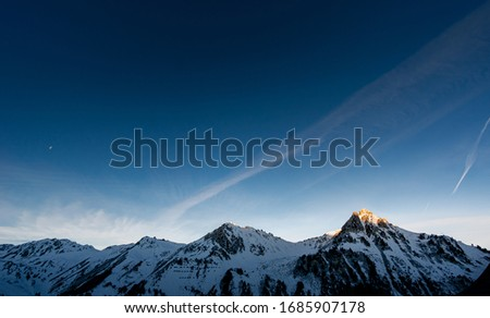 panoramic of mountains chain at sunrise. only one pic is illuminated
