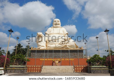 "Statue of Budai (Laughing Buddha) at Vinh Trang Temple in My Tho, Vietnam. Written mantra translates to: ""I bow to Maitreya, the honored future Buddha."" Royalty-Free Stock Photo #1685933680"