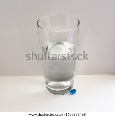 Transparent glass with water and blue oval tablet on a white background #1685938468