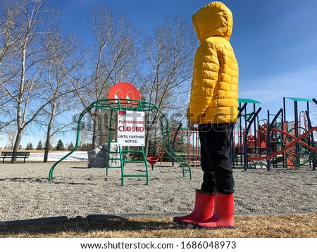 A lonely elementary school aged child standing and looking at an empty playground park closed due to coronavirus covid-19 sign in Calgary, Canada