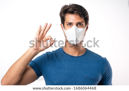 Handsome man brazilian showing okay gesture. Photo of healthy man wears protective mask against infectious diseases and flu. Health care concept.Mask prevent Covid 19 OK Leave space White background #1686064468