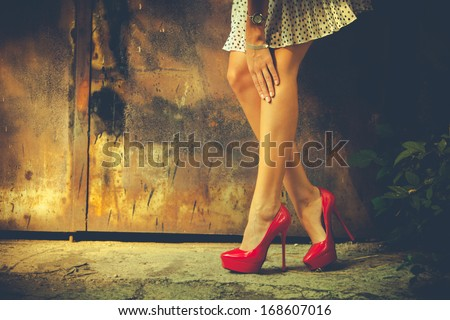 woman legs in red high heel shoes and short skirt outdoor shot against old metal door Royalty-Free Stock Photo #168607016