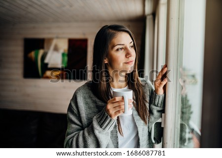Young woman spending free time home.Self care,staying home.Enjoying view,gazing through to the window.Quarantined person indoors.Serene mornings.Avoiding social contact. #1686087781