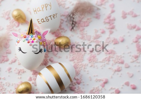 Minimal easter concept. Easter eggs in the form of a unicorn, and with a gold pattern on a white background. Flat lay. Copy space for text. The portfolio has more Easter pictures.