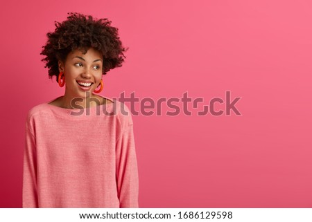 Studio shot of carefree happy Afro American woman looks aside with beaming smile, enjoys nice conversation, dressed in stylish outfit, concentrated aside, models against pink background, free space #1686129598