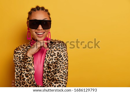 Beautiful charming lady smiles positively, has cheerful talk with interlocutor, keeps hand under chin, wears stylish outfit, big sunglasses, happy to buy new fashioable outfit, isolated on yellow wall #1686129793