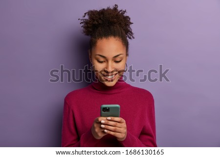Happy beautiful Afro American woman uses social media messanger on modern mobile phone, chats with friends, going to have video call, dressed in casual wear, makes shopping in internet store #1686130165