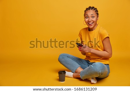Relaxed dark skinned woman sits crossed legs, dressed in casual t shirt and jeans, uses mobile phone, sends text messages, browses internet, drinks takeaway coffee, scrolls news, isolated on yellow Royalty-Free Stock Photo #1686131209