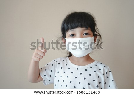Asian kid use medical mask or surgical mask to protect her from virus, sickness, Covit-19 and coronavirus infection. #1686131488