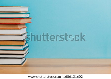 A simple composition of many hardback books, raw books on a wooden table and a bright blue background. back to school. Education. #1686131602