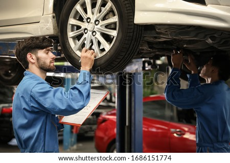 Auto mechanic checking problem for the car engine at the garage,technician or engineer professional work for customer #1686151774
