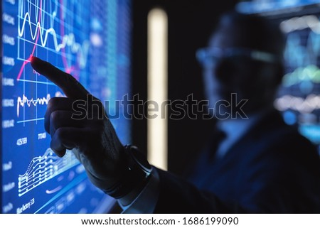 The old businessman working on the big blue screen with graphics #1686199090