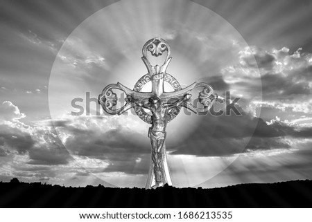 black and white image of Jesus Christ crucified with a background of clouds with sun rays