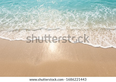 Blue ocean waves Sunlight Reflection Sand Beach background Royalty-Free Stock Photo #1686221443