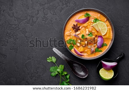 A Chicken Massaman Curry in black bowl at dark slate background. Massaman Curry is Thai Cuisine dish with chicken meat, potato, onion and many spices. Thai Food. Copy space. Top view #1686231982