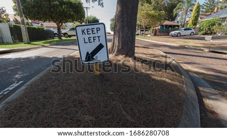 Keep left sign in road island in a suburban setting #1686280708