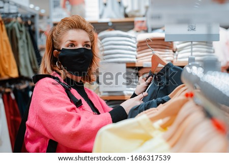 beautiful woman with phone bright pink shopping Mall coat with black protective mask on her face from virus infected air. concept of virus protection in the fashion, beauty, and shopping industries. #1686317539